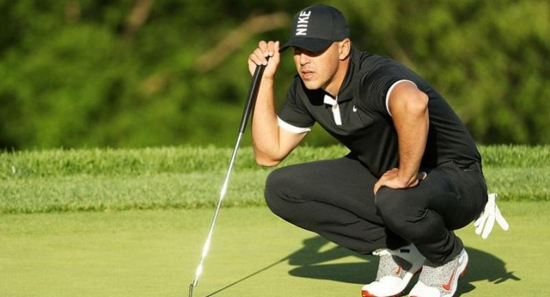 Brooks Koepka of the United States lines up a putt on the 15th green during the third round of the 2019 PGA Championship at the Bethpage Black course. / AFP