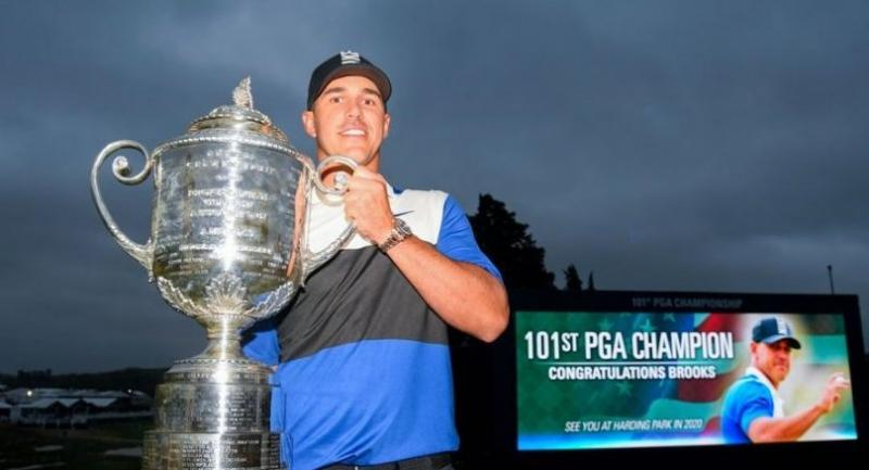 Brooks Koepka of the United States poses with the Wanamaker Trophy. / AFP