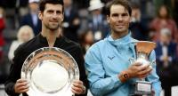 Rafael Nadal (R) of Spain poses with Novak Djokovic of Serbia after winning the ATP Masters tournament final tennis match at the Foro Italico in Rome. / AFP