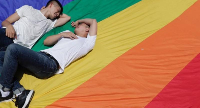 A same-sex married couple sit on a rainbow flag during the first day of civil registration for same-sex marriage in Taipei, Taiwan, 24 May.//EPA-EFE