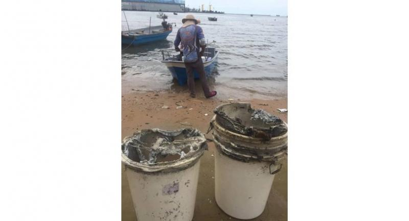 Local fishermen retrieve buckets of water from the sea near Laem Chabang Seaport in Chon Buri province yesterday.