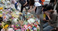 People pay their respects next to flower tributes at the crime scene where a man stabbed 19 people, including children, in Kawasaki on May 29.//AFP