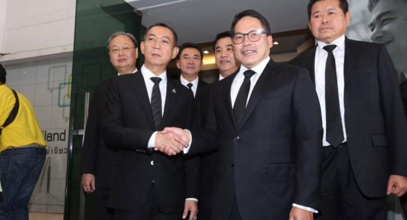 Phalang Pracharat Party leader Uttama Savanayana, right, shakes hands with Democrat Party secretary-general Chalermchai Sri-on on Monday when Uttama sent an official invitation to the Democrats to join a coalition government.