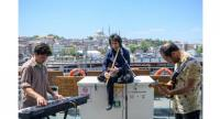 Musicians Oguzhan Erdemm plays the ney, Eren Koc on keyboards and Zafer Saka on guitar during a ferry trip on the Bosphorus from Kadikoy to Eminonu, in Istanbul.