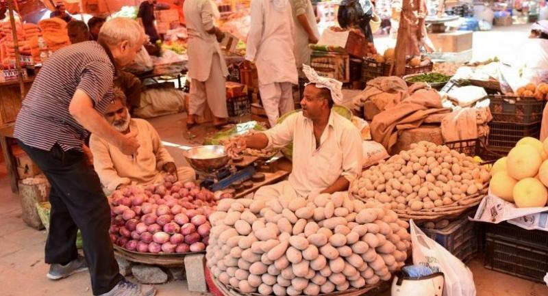 Pakistanis gather around vegetable stalls in Karachi. /AFP