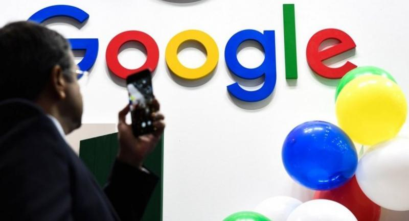 In this file photo taken on May 16, 2019 A man takes a picture with his mobile phone of the logo of the US multinational technology and Internet-related services company Google as he visits the Vivatech startups and innovation fair, in Paris./AFP