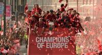 Liverpool's German manager Jurgen Klopp (C) holds the European Champion Clubs' Cup trophy during an open-top bus parade around Liverpool. / AFP