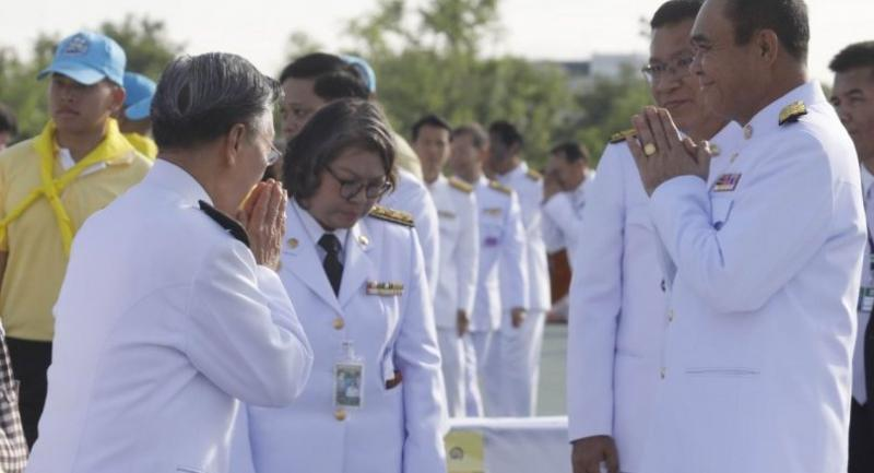 Prime Minister Prayut Chanocha greets House Speaker Chuan Leekpai at Sanam Luang yesterday when they joined others in offering alms to 410 Buddhist monks as part of merit-making to mark Her Majesty the Queen's birthday. BY Prasert Thepsri
