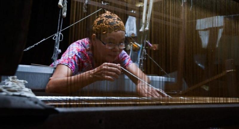 Rampai Sripetch, a 65-year-old Thai Muslim woman, weaving silk fabric on a loom at a workshop near Darul Falah mosque in Bangkok. /AFP
