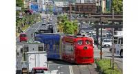 "A streetcar designed to look like the character Wilson from the ""Chuggington"" animated series travels the streets of Okayama."