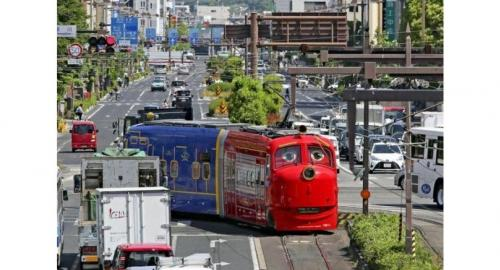 """A streetcar designed to look like the character Wilson from the """"Chuggington"""" animated series travels the streets of Okayama."""
