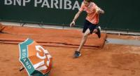 A ball boy collects an umbrella on the court due to heavy wind. / AFP