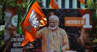 File photo: A billboard with an image of Indian Prime Minister Narendra Modi is surrounded by Bharatiya Janata Party (BJP) flags. // AFP PHOTO