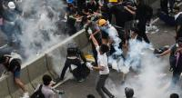 A protester (C) throws back a tear gas during clashes with police outside the government headquarters in Hong Kong on June 12, 2019. // AFP PHOTO
