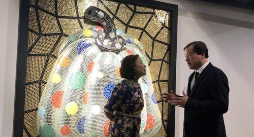 """Filipino collector Maria Clara Camacho chats with Apinan Poshayananda in front of Yayoi Kusama's polkadot masterpiece """"Pumpkins"""" at BAB Box in Bangkok. Nation/Phatarawadee Phataranawik"""