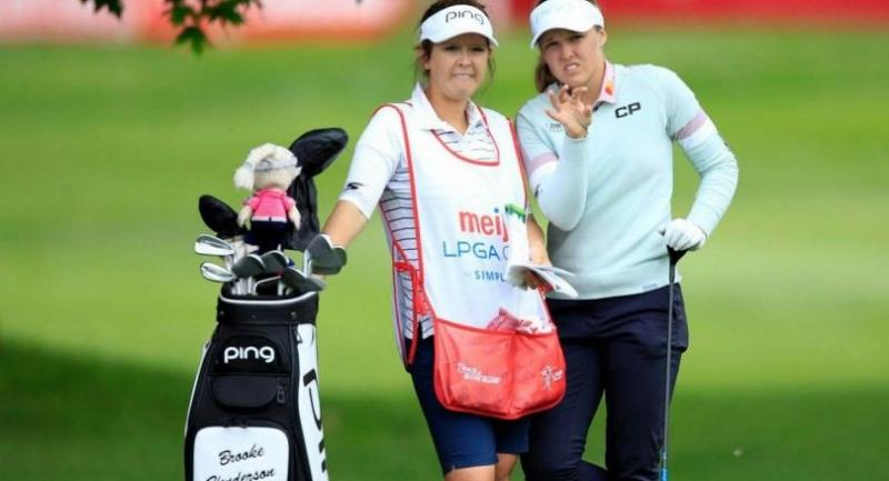 Brooke Henderson of Canada and her caddie talk before hitting her second shot on the 10th hole. / LPGA Photo