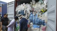 This picture taken on June 15, 2019 shows Indonesian customs officers from the local environment office examining one of 65 containers full of imported plastic rubbish, at the Batu Ampar port in Batam.//AFP