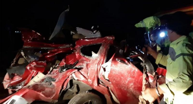 This handout picture taken early on June 17, 2019 and released by West Java Police shows police officers inspecting the wreckage of a car involved in an accident with a coach on a toll road in Majalengka, West Java. // AFP PHOTO