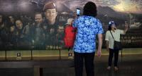 Visitors taking photos in front of a mural, illustrating the rescue of the 12 boys from the