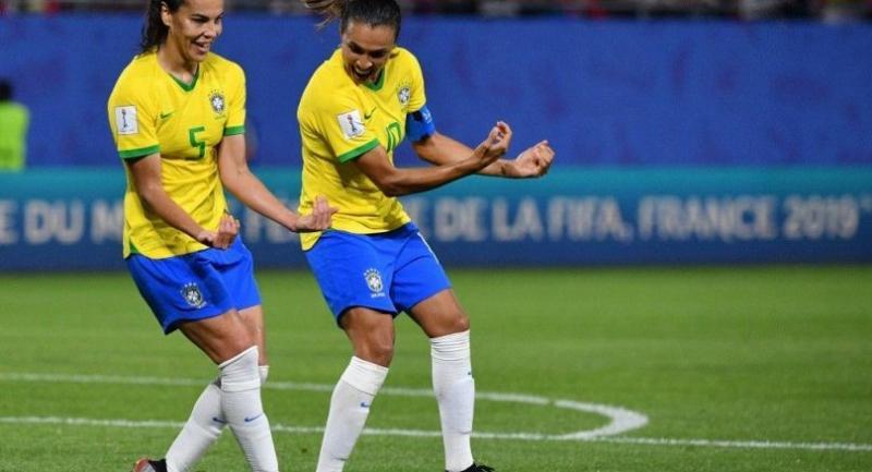 Brazil's forward Marta (R) celebrates with Brazil's midfielder Thaisa. / AFP