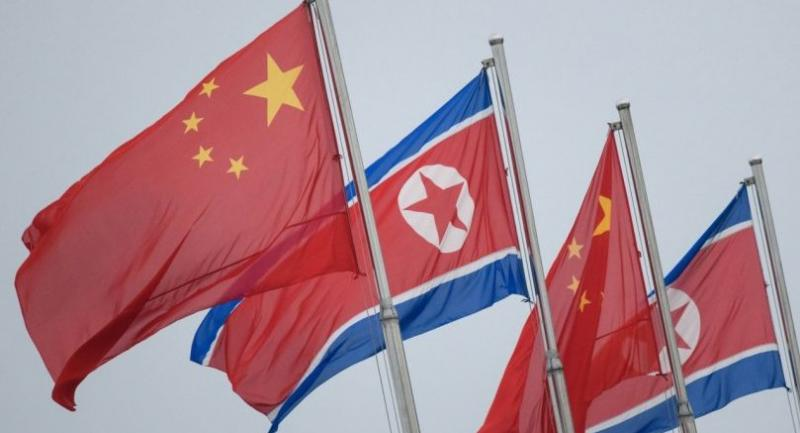 North Korean and Chinese flags fly in Pyongyang on June 19.//AFP