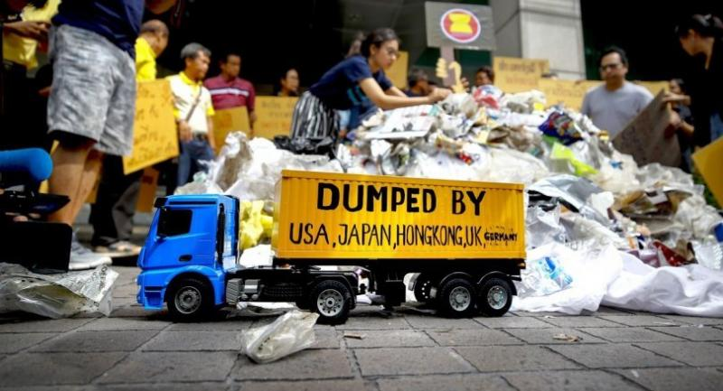 Greenpeace activists dump garbage and hold placards calling for a halt to international waste dumping, in front of the Foreign Ministry in Bangkok yesterday. // EPA-EFE PHOTO