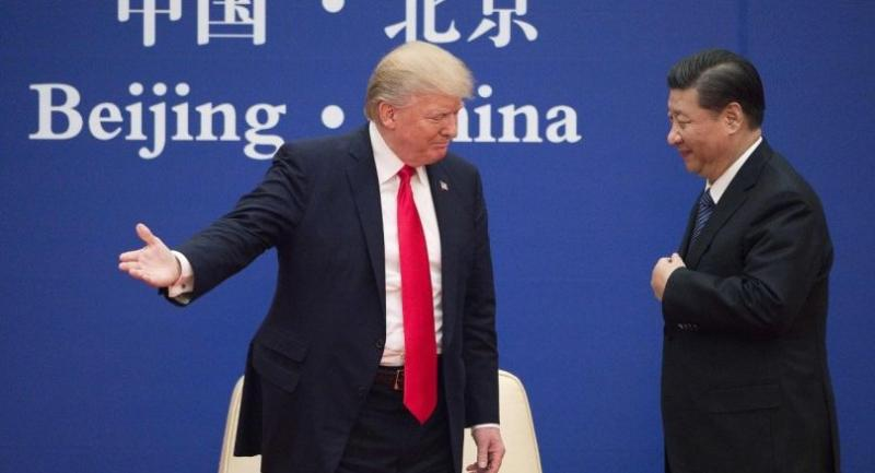 File photo :  US President Donald Trump (L) gestures next to China's President Xi Jinping during a business leaders event at the Great Hall of the People in Beijing in 2017. //AFP
