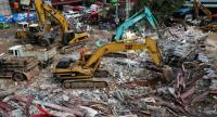 Rescue workers use earthmovers to clear debris as they search for victims a day after an under-construction building collapsed in Sihanoukville on June 23.//AFP
