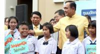 Prime Minister General Prayut Chan-o-cha teases a young beneficiary of the Equitable Education Fund (EQF) that provides scholarships for low-income children, as EQF chair Prasarn Trairatvorakul looks on at Government House yesterday.