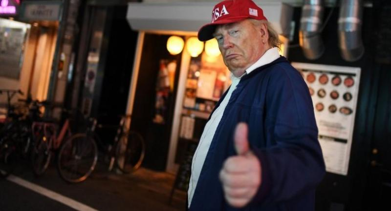 A Donald Trump impersonator gives the thumb up as he walks in a street of Osaka during the G20 Osaka Summit on June 28, 2019. (Photo by Charly TRIBALLEAU / AFP)