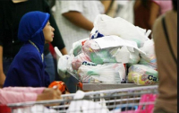 A customer of a supermarket pushes a trolley full of goods in plastic bags. (Harian Kompas/Yuniadhi Agung)