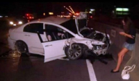 "Wealthy teenager ""Praewa"" leans against a road barrier and uses her phone to send messages just moments after causing the fatal crash of December 27, 2010."