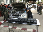 Bags of amphetamines are laid out as a search of the abandoned vehicle is carried out in Chiang Saen district on Wednesday.