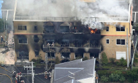 Smoke and flames are seen at a studio building belonging to Kyoto Animation Co in Fushimi Ward, Kyoto, on Thursday./The Japan News photo