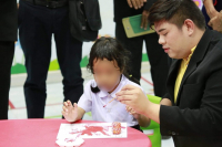 An autism girl colors a drawing at the Nakhon Phanom Special Education Centre.
