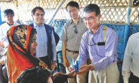 Visiting Japanese Foreign Minister Taro Kono receives a paper flower as a gift from a Rohingya girl as he arrives at a Rohingya camp in Cox's Bazar's Kutupalong yesterday. Photo: Anisur Rahman