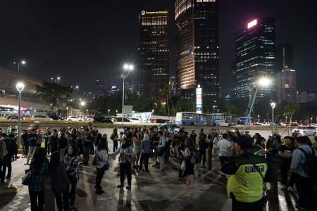 Employees gather outside their office buildings following an earthquake that struck Banten on Friday. (Antara/Dwi Prasetya)