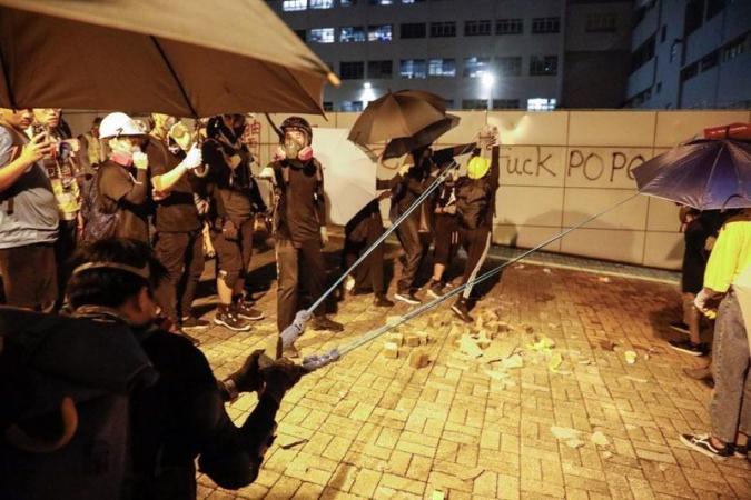 Protesters use a large self-made sling to hurl bricks at Tsim Sha Tsui police station, Hong Kong, Aug 3, 2019. (PHOTO / CHINA DAILY)