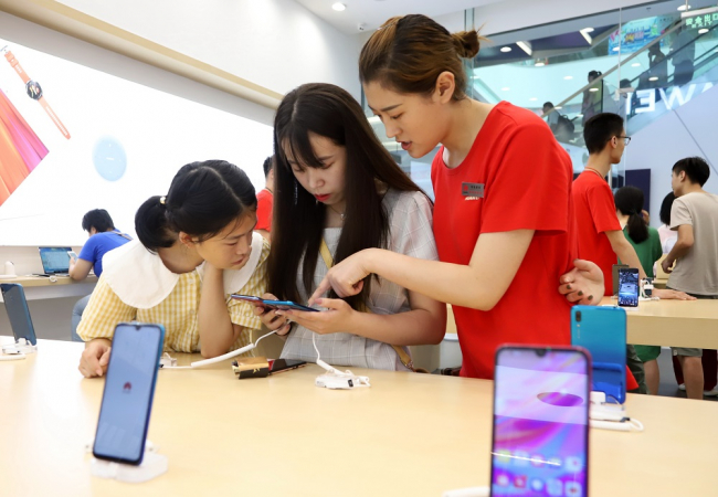 Consumers try out Huawei smartphones at a store in Qingdao, Shandong province. [WANG PEIKE/FOR CHINA DAILY]