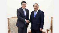 Prime Misister Nguyen Xuan (R) received Governor of the Bank of Thailand Veerathai Santiprabhob in Hanoi on August 5.