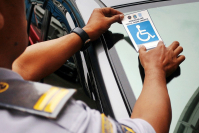 Waiver: A Jakarta Transportation Agency official affixes a disability sticker to a car parked at the agency's office in Central Jakarta on Tuesday that exempts the driver from the odd-even license plate traffic restriction. (The Jakarta Post/Umair Rizaludin )