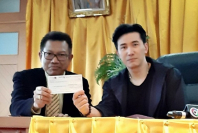 "File Photo: TV news anchor Kanchai ""Noom"" Kamnerdploi, right, and lawyer Decha Kittiwittayanan hold up a cheque for Bt800,000, which will be added to the Bt41.75 million already given to court in compensation for the nine deaths and injuries sustained from a 2010 road accident involving an underage driver, known by her nickname ""Praewa""."
