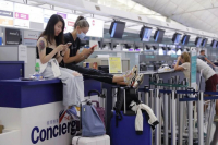 Stranded travellers sit on the check-in counters at the Hong Kong International Airport yesterday. (Photo: AP)