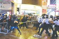 Radical protesters attack police officers with metal rods at an unauthorized assembly in Hong Kong on Sunday.