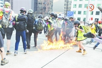 A gasoline bomb thrown by radicals lands in the crowd of journalists during Saturday's protest.(PHOTO / CHINA DAILY)