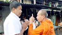 Chatchart speaks with a monk during a political campaign in March this year.