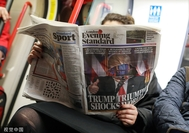 A commuter reads a copy of the London Evening Standard newspaper on a subway train in London. [Photo/VCG]