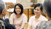 In this file photo, Indonesian caregivers Ema Yuliana, 26 ® and Citra Valentine, 25, chat with residents of Sawayakaen,a nursing care home in Hodogaya, Yokohama, on March 28, 2012. Yuliana and Valentine , who have worked under the Economic Partnership Agreement, passed the national care worker exam conducted by the Health, Labor and Welfare Ministry. (The Yomiuri Shimbun via AP Images)