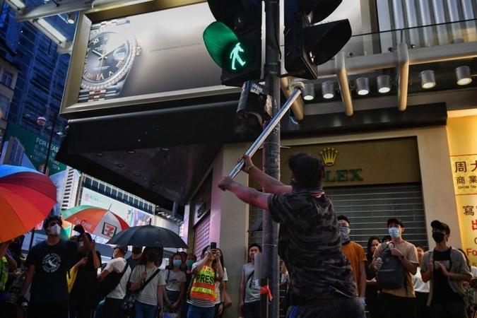 A protester attempts to vandalise a traffic light in Mong Kok, Hong Kong, on Oct 13, 2019.ST PHOTO: CHONG JUN LIANG