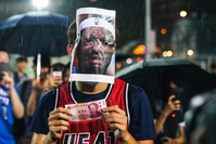 A basketball fan wears a Miami Heat jersey with a Lebron James mask on, licking a 100 Chinese yuan bill on Tuesday in Southorn Playground, Wan Chai, Hong Kong. Photo: Getty Images